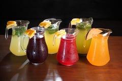 Limonata nella brocca e nei limoni con la menta sulla tavola dell'interno Estinzione della sete e rinfrescare le bevande fotografia stock