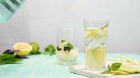Limonata o cocktail di mojito con il limone, la limetta ed il basilico video d archivio