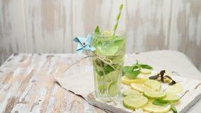 Limonata o cocktail di mojito con il limone, la limetta ed il basilico stock footage