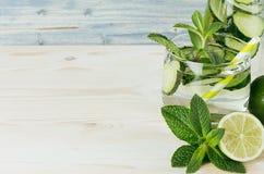 Limonata trasparente fresca di estate in vetro con paglia e gli ingredienti come confine - cetriolo, calce, menta sul bordo di le immagine stock libera da diritti