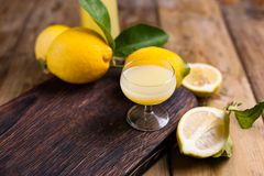 Limoncello and lemons on a wooden board. The traditional alcohol royalty free stock image