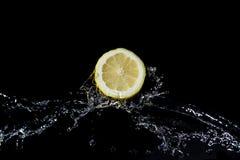 Limone affettato con la spruzzata dell'acqua con fondo nero Fotografia Stock Libera da Diritti