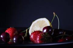 Limone, ciliege e fragole in vassoio d'acciaio rotondo su fondo scuro, primo piano, luce della luna Immagine Stock