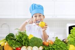 Limone di taglio del bambino in cucina immagini stock