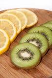 Limone e kiwi affettati su un bordo di legno Immagine Stock