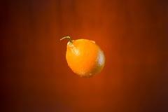 Limone e spruzzata di acqua su fondo arancio Fotografie Stock