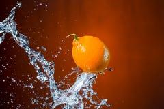 Limone e spruzzata di acqua su fondo arancio Immagine Stock Libera da Diritti