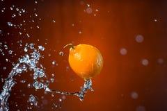Limone e spruzzata di acqua su fondo arancio Fotografia Stock Libera da Diritti