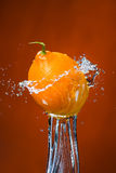 Limone e spruzzata di acqua su fondo arancio Immagini Stock Libere da Diritti