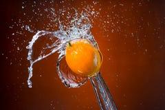 Limone e spruzzata di acqua su fondo arancio Fotografie Stock Libere da Diritti