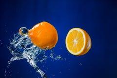 Limone e spruzzata di acqua su fondo blu Fotografia Stock Libera da Diritti