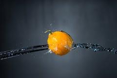 Limone e spruzzata di acqua su fondo grigio Immagine Stock Libera da Diritti