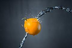 Limone e spruzzata di acqua su fondo grigio Immagini Stock