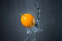 Limone e spruzzata di acqua su fondo grigio Fotografie Stock