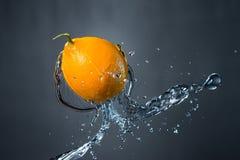 Limone e spruzzata di acqua su fondo grigio Fotografia Stock Libera da Diritti