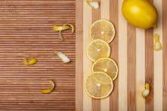 Limone giallo fresco con le fette sul bordo di bambù di legno della cucina Immagine Stock