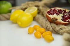Limone, granato e frutta sulla tavola bianca Fotografie Stock Libere da Diritti