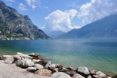 Limone, Lake Garda, Italy. Image shows Limone on the left, Lake Garda in the middle, some mountains on both sides and stony beach in the front Royalty Free Stock Photo