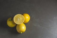 Limones de la fruta fresca con la rebanada del limón en la tabla negra Imagenes de archivo