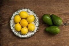 Limones en la placa y los aguacates blancos sobre fondo rústico Foto de archivo