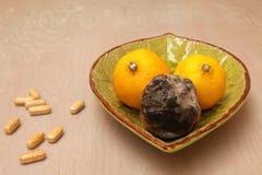 Limones en un cuenco con las tabletas de la vitamina C Foto de archivo