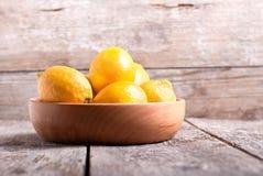 Limones en un cuenco de madera en la tabla Imagenes de archivo