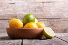 Limones en un cuenco de madera en la tabla Foto de archivo