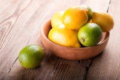 Limones en un cuenco en una tabla Foto de archivo