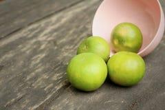 Limones en un cuenco rosado en un fondo de madera Imágenes de archivo libres de regalías