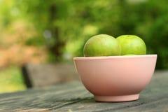 Limones en un cuenco rosado en un fondo de madera Foto de archivo
