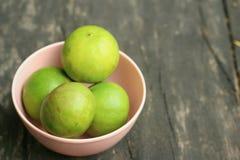 Limones en un cuenco rosado en un fondo de madera Foto de archivo libre de regalías