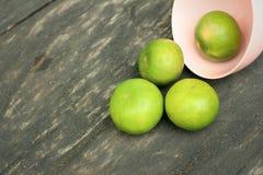 Limones en un cuenco rosado en un fondo de madera Fotos de archivo libres de regalías