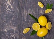 Limones enteros con las hojas y corte en pedazos, en superficie de madera Foto de archivo libre de regalías