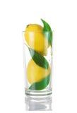 Limones enteros en un vidrio Imagen de archivo libre de regalías