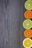 Limones, mandarinas y cales en la tabla de madera gris Foto de archivo
