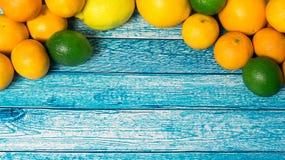 Limones, naranjas y cales Naranjas, mandarinas, cales y limones Sobre fondo de madera de la tabla con el espacio de la copia Fotos de archivo