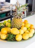 Limones, piña y cales en un cuenco en la barra Imágenes de archivo libres de regalías