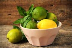 Limones y cales en un cuenco Foto de archivo libre de regalías