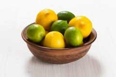 Limones y cales en un cuenco de la arcilla Foto de archivo