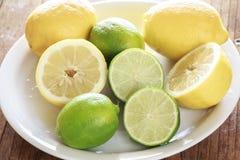 Limones y cales en un plato Imágenes de archivo libres de regalías