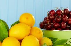 Limones y cerezas rojas maduras en colador verde Foto de archivo libre de regalías