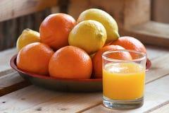 Limones y jugo anaranjados Imagen de archivo