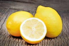 Limones y mitad en un fondo de madera rústico Imagen de archivo