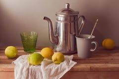 Limones y pote del té en la tabla de madera Vida rústica del vintage aún Foto de archivo libre de regalías