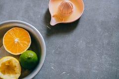 Limoni, calce, arancio in un di piastra metallica, gli spremiagrumi dell'agrume Fotografia Stock