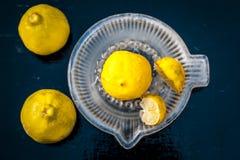Limoni con lo spremitoio del limone su superficie di legno immagine stock