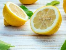 Limoni del primo piano e foglie freschi dei limoni sul backgro di legno misero Fotografia Stock Libera da Diritti