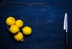 Limoni e coltello sul tagliere sulla tavola di legno Immagini Stock