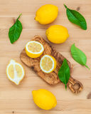 Limoni e foglie freschi dei limoni su fondo di legno rustico Fre Fotografia Stock