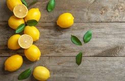Limoni e foglie freschi su fondo Immagini Stock